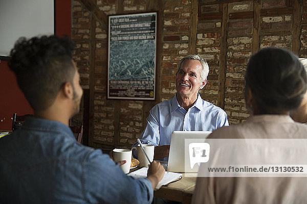 Geschäftsmann im Gespräch mit Kollegen während eines Treffens im Café