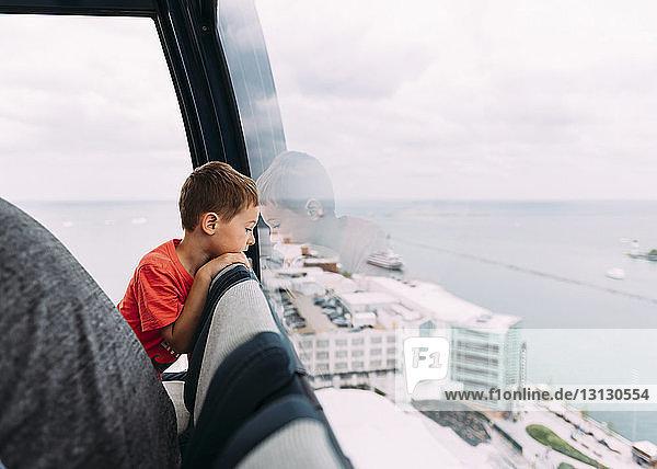Boy looking through window while sitting in Gondola