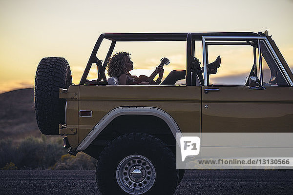 Woman playing guitar while sitting in off-road vehicle against sky during sunset