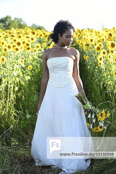 Braut hält Brautstrauss  während sie inmitten von Sonnenblumen am Bauernhof gegen den Himmel steht