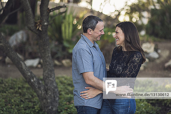 Cheerful couple looking each other face to face at park