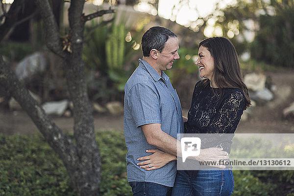 Fröhliches Paar  das sich im Park Auge in Auge gegenübersteht