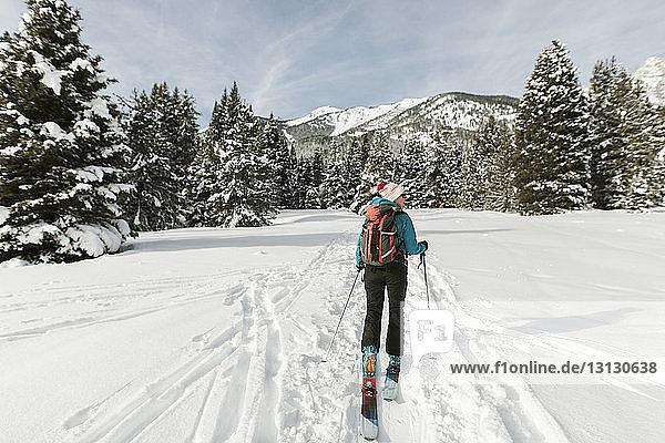 Rückansicht einer Frau mit Himmel  die auf einem schneebedeckten Feld gegen den Himmel läuft