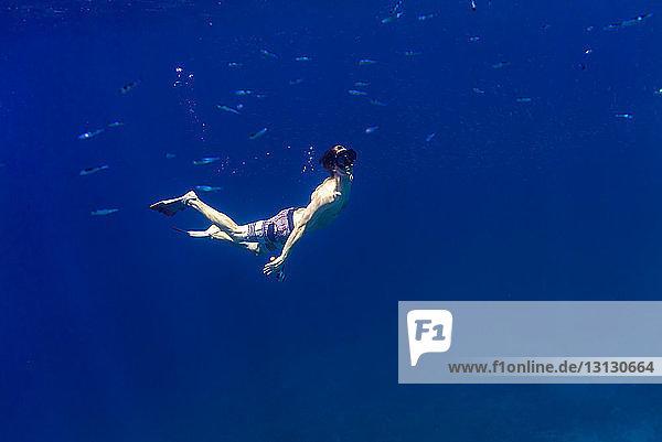 Mann schwimmt unter Wasser im Meer