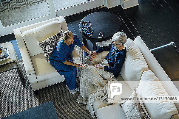 High angle view of home caregiver showing tablet computer to senior woman while sitting on sofa in living room