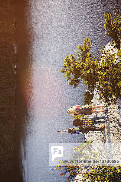 High angle view of friends standing on rock by lake