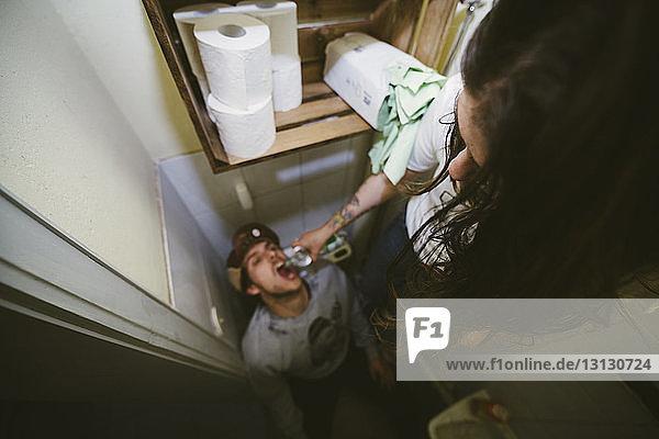 Schrägaufnahme einer Frau  die einem Mann im Badezimmer Trinkwasser gibt