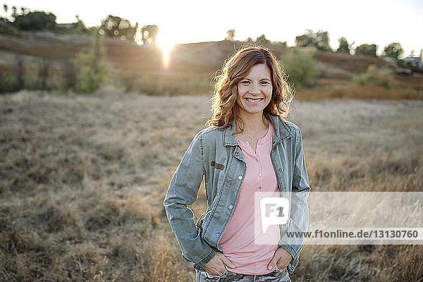 Porträt einer lächelnden Frau  die auf einem Grasfeld gegen den Himmel im Wald steht