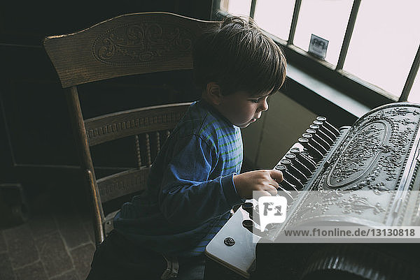 High angle view of boy playing musical instrument at home