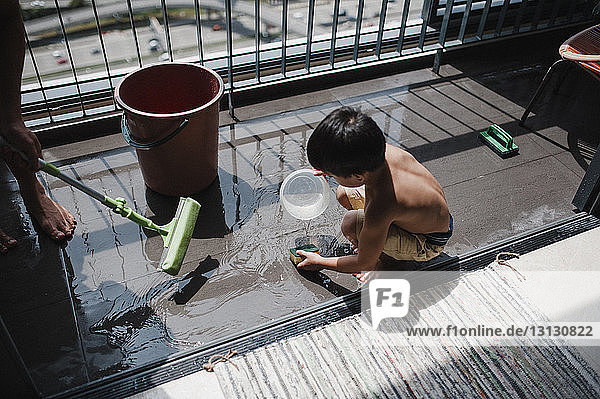 High angle view of father and son cleaning balcony