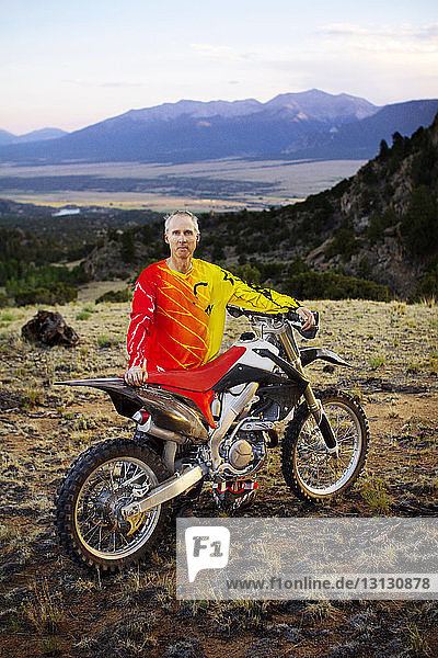 Portrait of man standing with dirt bike against mountain