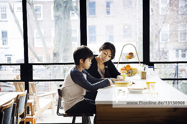 Mother teaching son on table against window at home