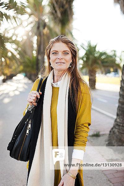 Porträt einer selbstbewussten reifen Frau mit stehendem Portemonnaie in der Stadt