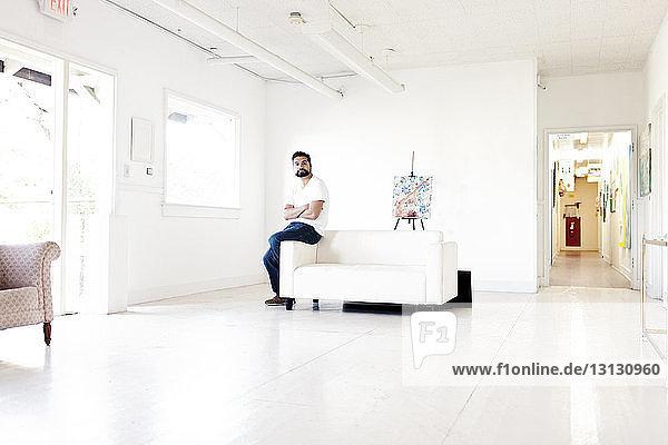 Confident artist sitting on handrest of sofa in art studio