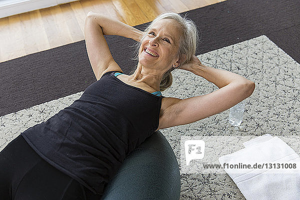 Lächelnde ältere Frau mit Händen hinter dem Kopf auf dem Fitnessball liegend  während sie zu Hause Sport treibt