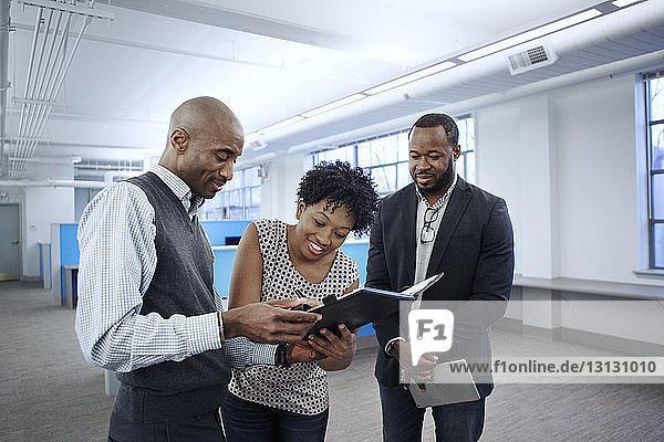 Geschäftsleute schauen auf eine Kollegin  die im Amt Dokumente unterzeichnet