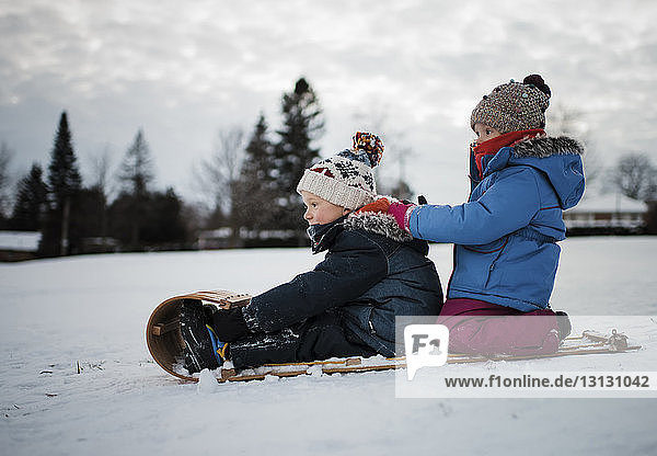 Side view of siblings on sled against cloudy sky
