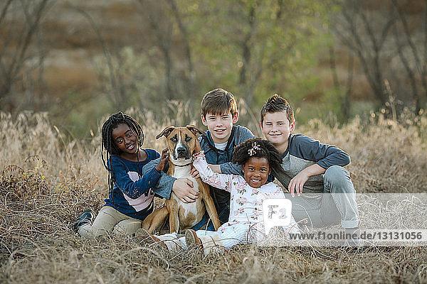 Porträt von lächelnden Geschwistern mit Hund auf Grasfeld im Wald sitzend