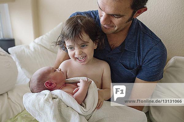Fröhliche Schwester spielt zu Hause mit dem neugeborenen Bruder des Vaters