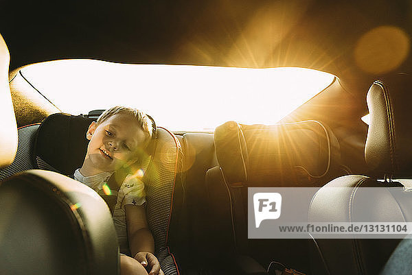 Boy relaxing while sitting in car