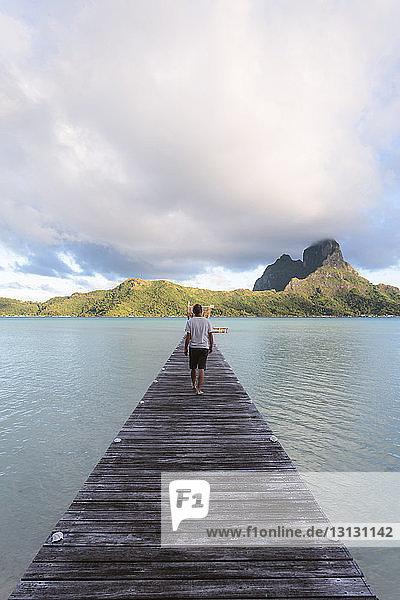 Rückansicht eines Mannes  der auf einem Steg über der Lagune vor bewölktem Himmel geht