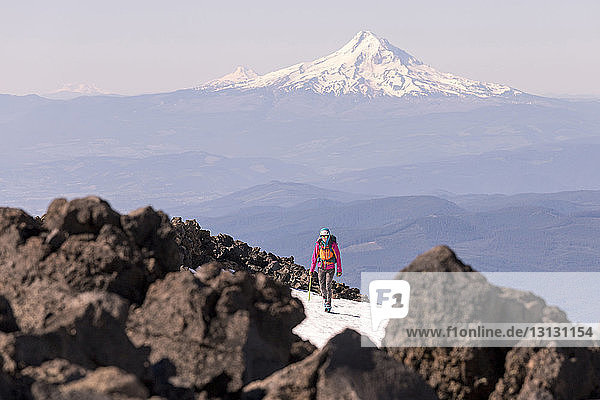 Frau wandert im Winter gegen schneebedeckten Berg