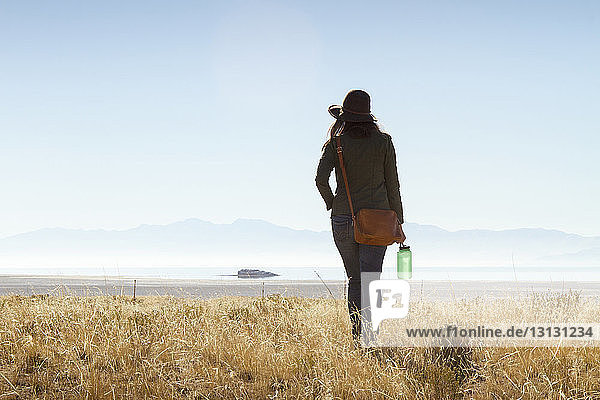 Rear view of woman walking on grassy field against clear sky at Antelope Island