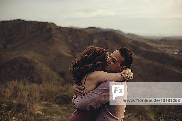 Seitenansicht eines liebenden jungen Paares  das sich auf dem Feld gegen Berge umarmt