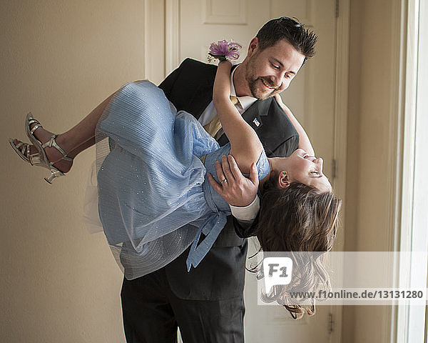 Father lifting daughter while dancing at home