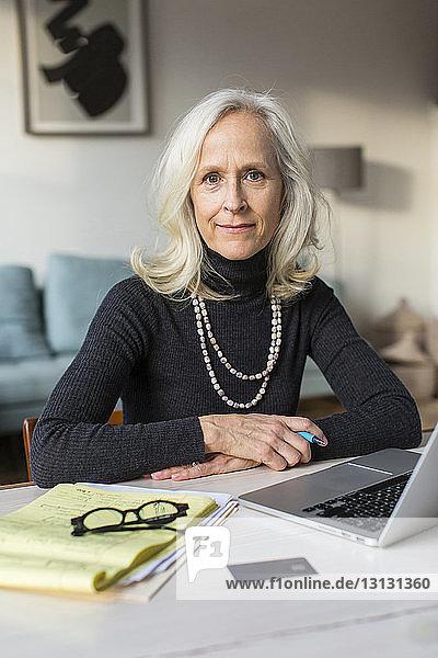 Porträt einer selbstbewussten älteren Frau mit Laptop-Computer auf dem Tisch zu Hause