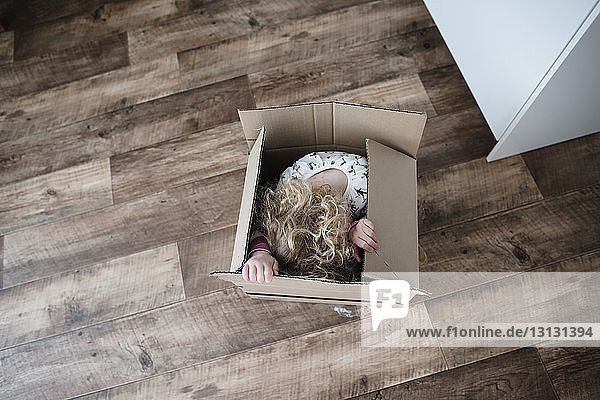 High angle view of happy girl sitting in cardboard box at home