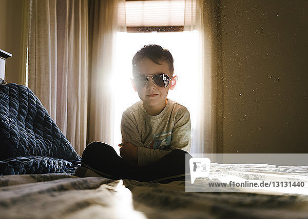Portrait of boy with arms crossed wearing sunglasses while sitting on bed at home