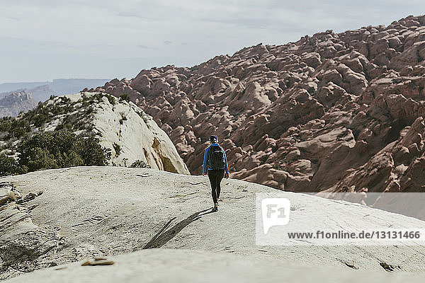 Rear view of hiker with backpack walking on rock during sunny day