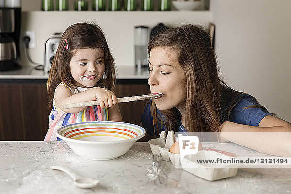 Daughter feeding food to mother in kitchen at home