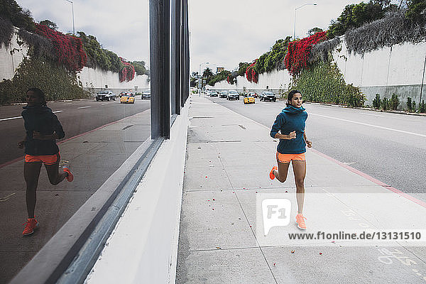Junge Frau joggt auf Fußweg