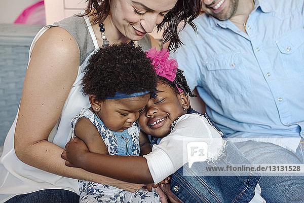 Glückliche Eltern mit zu Hause sitzenden Töchtern