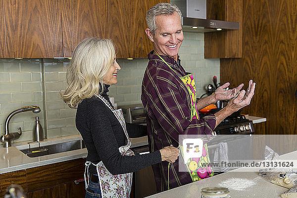 Lächelnde Frau bindet Männern die Schürze zu  während sie zu Hause in der Küche steht