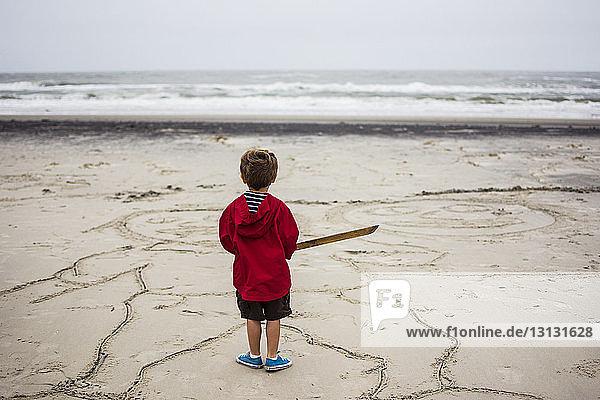 Rückansicht eines Jungen  der auf Sand am Strand steht