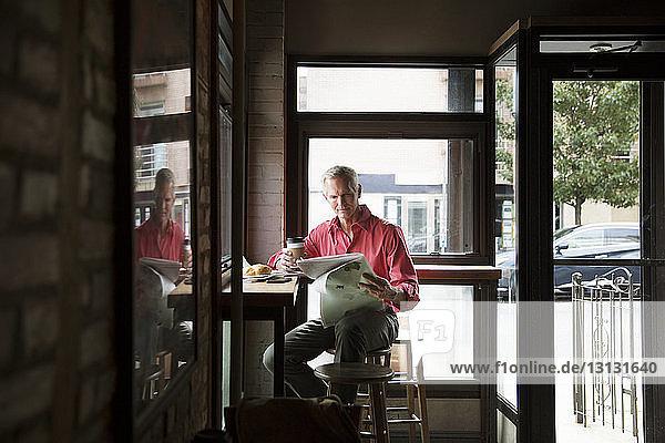 Reifer Mann liest Zeitung  während er Kaffee im Café trinkt