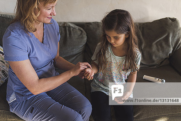 High angle view of doctor checking pulse of girl while sitting on sofa at home