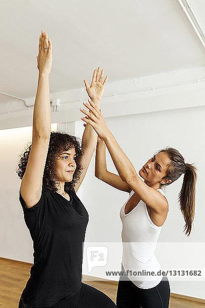 Yogalehrerin führt Frau beim Üben im Yogastudio