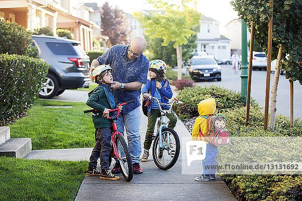Vater bereitet Söhne auf Radfahren vor  während er vor dem Haus steht