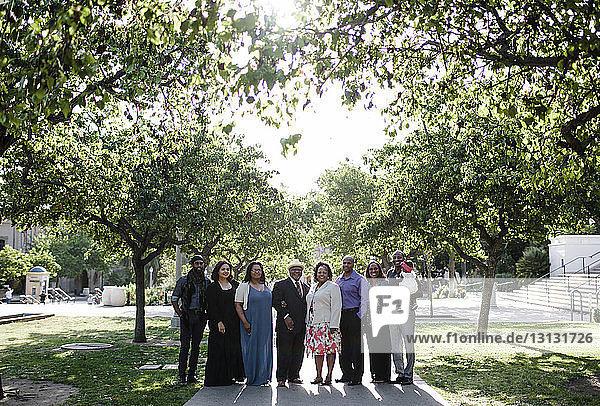 Porträt einer glücklichen Familie  die auf einem Fußweg im Park steht