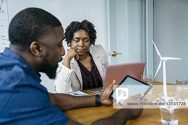 Geschäftsmann zeigt einer Kollegin ein Tortendiagramm in einem digitalen Tablett
