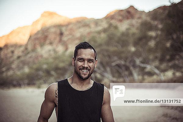 Porträt eines lächelnden Mannes an einem Berg in der Wüste