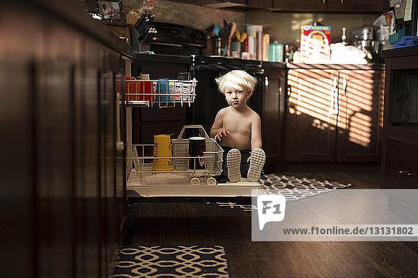 Portrait of boy sitting on drawer in kitchen