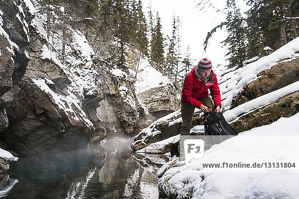 Hiker with backpack standing on snow covered rocks by stream at forest