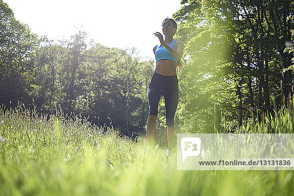 Low angle view of woman running on grassy field in park