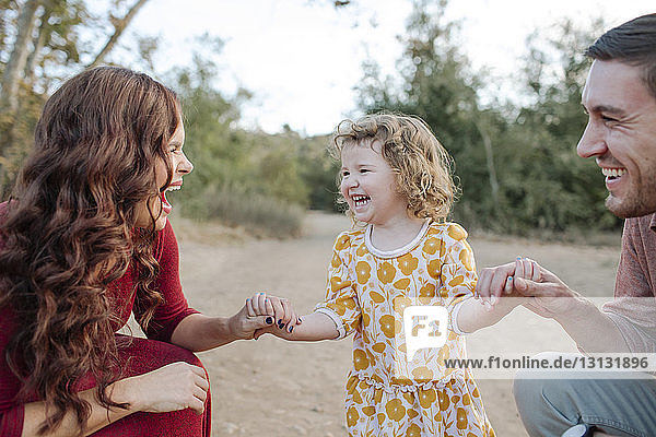 Man looking at cheerful mother with daughter