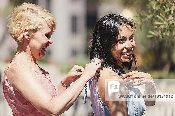 Glückliche Frau bindet Schleife auf dem Kleid eines Freundes an einem sonnigen Tag